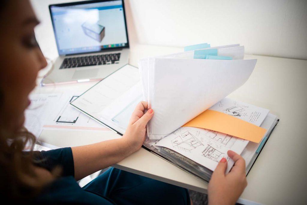 Jennifer Colajezzi bladert door haar map opzoek naar één van haar interieurontwerpen.