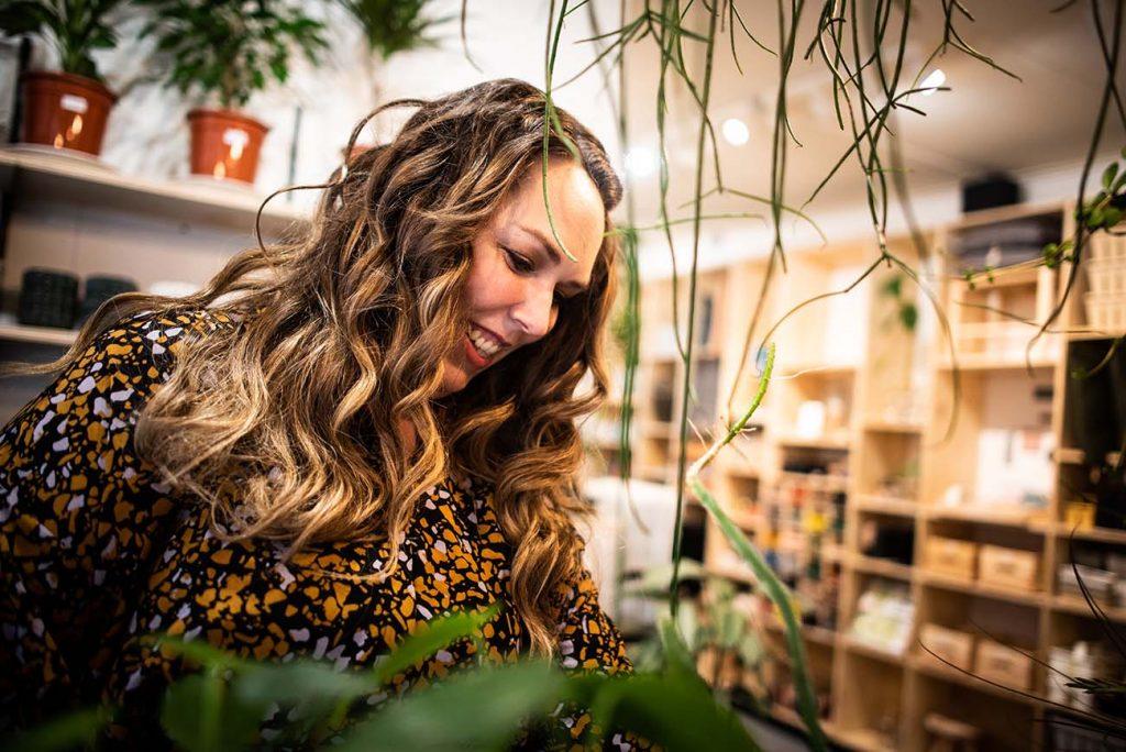 Jennifer Colajezzi staat in een winkel verschillende planten te bekijken ter invulling van haar interieurontwerp.