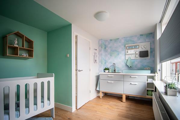 Mintgroen en licht blauw babykamer behang met grijze op maat gebouwde commode inclusief wasbak