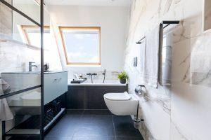 Zwart-wit badkamerontwerp met groene badmeubel.