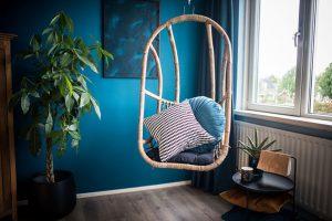 Thuiswerkplek met bamboe hangstoel en aqua blauwe wand.