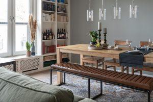 Een mooi ingerichte eetkamer met eikenhouten eettafel en lederen bank van goossens.